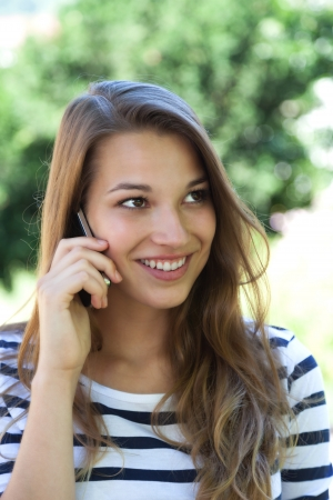 Young woman smiling on the phone in a park  photo