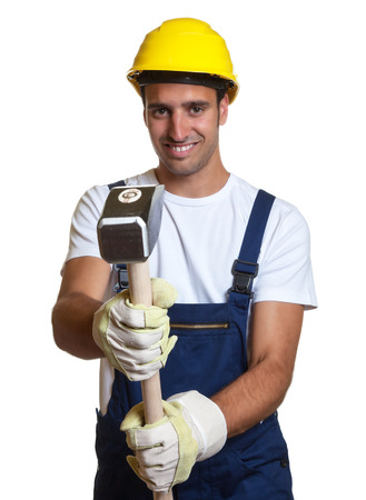 Laughing latin worker using a sledgehammer Banco de Imagens