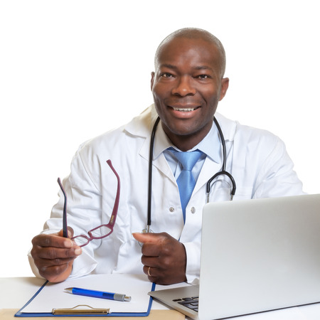 practitioner: African doctor on a desk with glasses in his hand