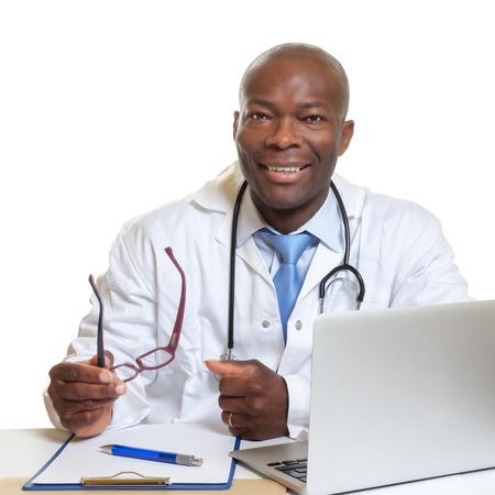 Afrikaanse arts op een bureau met een bril in zijn hand Stockfoto