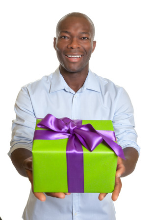 Laughing african man showing a gift for christmas  photo
