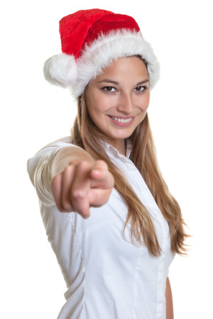 Beautiful woman with christmas hat pointing at camera Stock Photo - 23247584