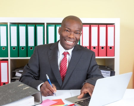 Laughing african businessman writing a message photo