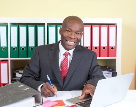 Laughing Afrikaanse zakenman schrijven van een bericht