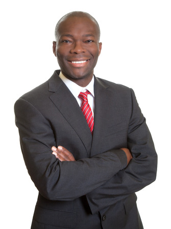 African businessman with crossed arms laughing at camera photo