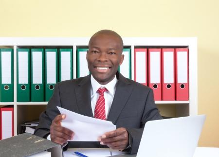Lachende Afrikaanse zakenman het lezen van een brief