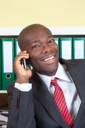 African businessman laughing at phone photo