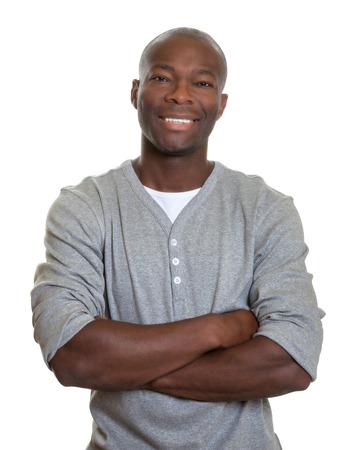 Laughing Afrikaanse man met in een grijs overhemd met gekruiste armen Stockfoto