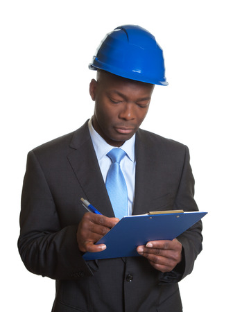 engineering clipboard: African architect writing message on clipboard Stock Photo
