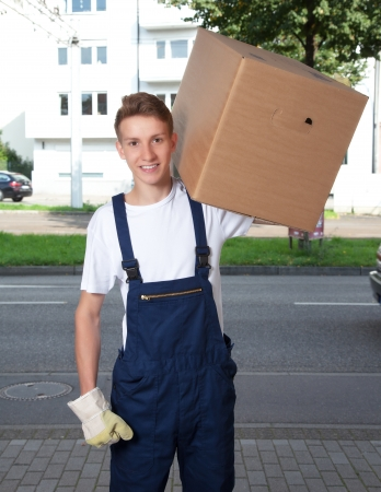 Young man carrying a box photo