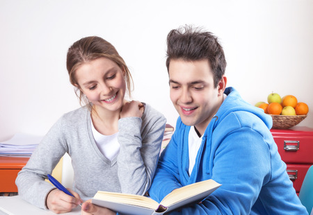Laughing students reading in a book photo