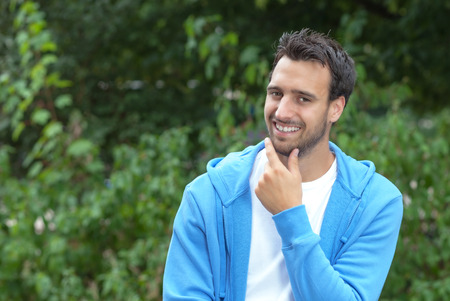 Attractive latin guy looking at camera in a park photo