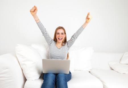Cheering young woman with notebook on a sofa