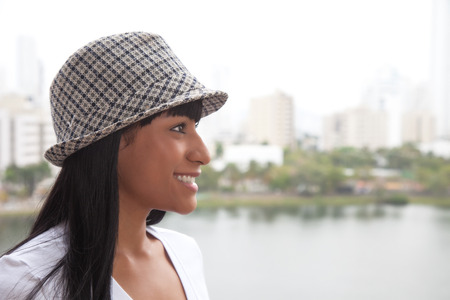 Laughing brazilian woman with hat looking sideways photo