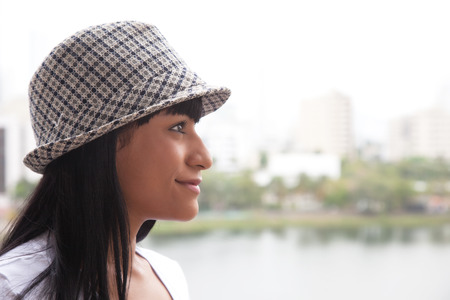 Smiling brazilian woman with hat looking sideways Stock Photo