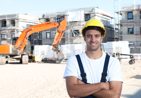 house worker: Laughing latin construction worker with crossed arms and red excavator