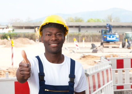 Laughing african worker at construction site showing thumb up  photo