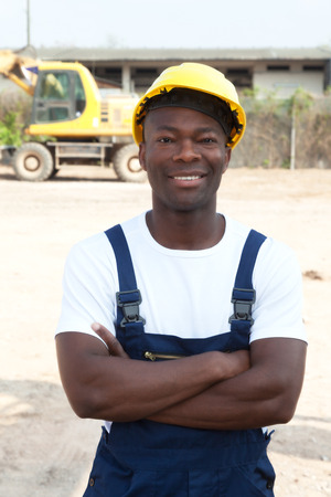collar: Standing african worker with crossed arms at construction site