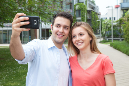 Young couple taking a selfie with mobile phone photo