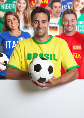 Laughing brazilian soccer fan with other fans behind signboard photo