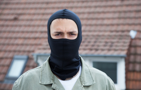 Masked burglar with roofs in the background photo