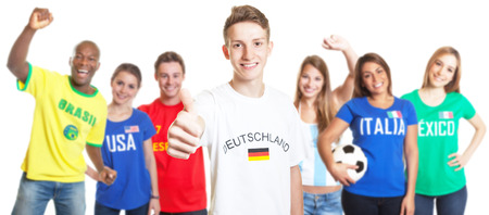 German soccer with blond hair showing thumb with other fans photo