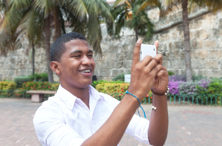 Attractive guy taking a picture with phone photo