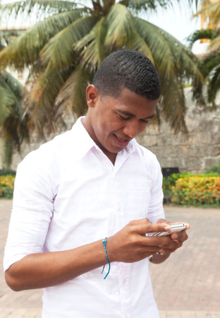 Caribbean guy writing a text message photo