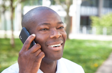African man talking at phone outside in a park photo