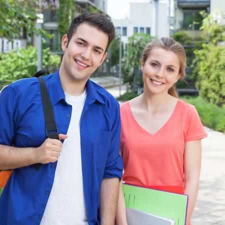 Twee studenten op de campus lachen naar de camera