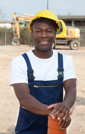 road worker: Standing african construction worker with pipe