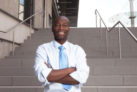 Afrikaanse zakenman met een trap op de achtergrond