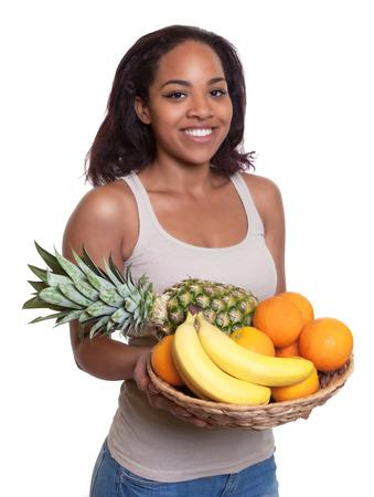 persona de pie: Mujer africana con una cesta de frutas