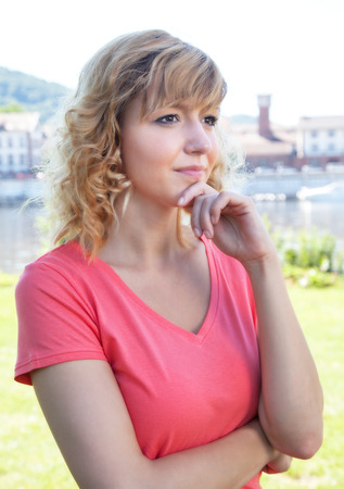 Thoughtful woman in a pink shirt outside