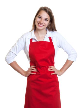 Staande serveerster met rode schort en gekruiste armen Stockfoto