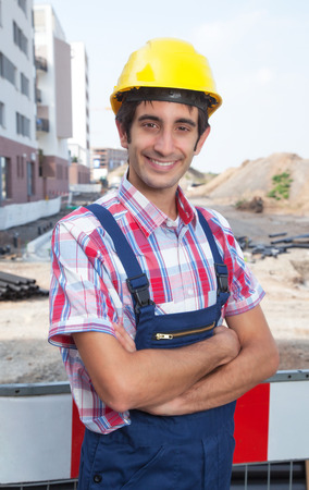 dug well: Construction worker with black hair and crossed arms