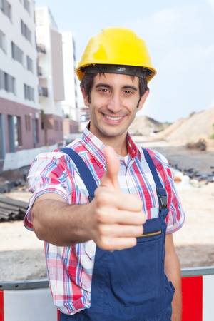 dug well: Construction worker with black hair showing thumb up