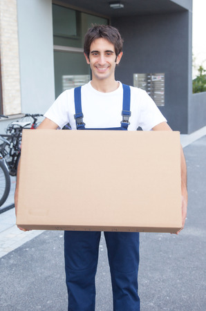 Laughing hispanic worker with box photo