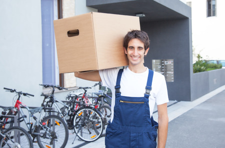 Hispanic worker with box in front of a building photo
