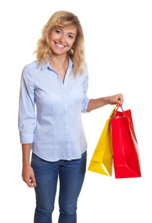 cabello rubio: Mujer de risa con el pelo rubio rizado y dos bolsas de la compra