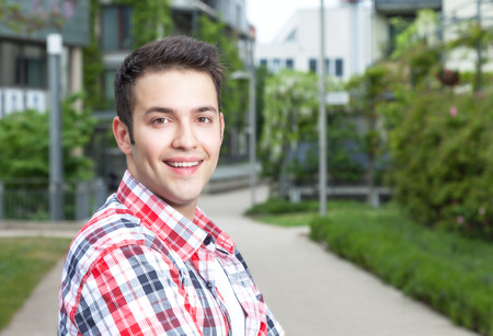 checked shirt: Smart student with checked shirt laughing at camera Stock Photo