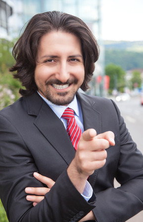 Pointing turkish businessman with suit in front of his office photo