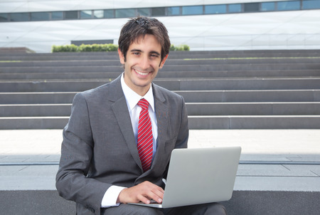 Laughing businessman with black hair and computer photo