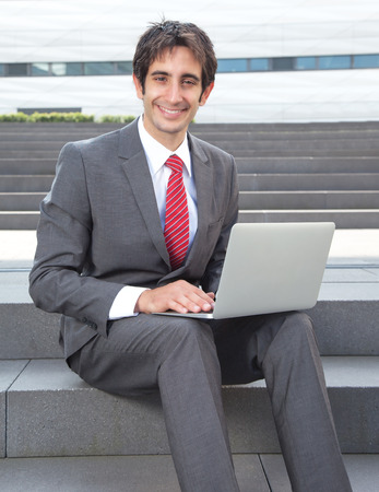 Attractive businessman with black hair and computer photo
