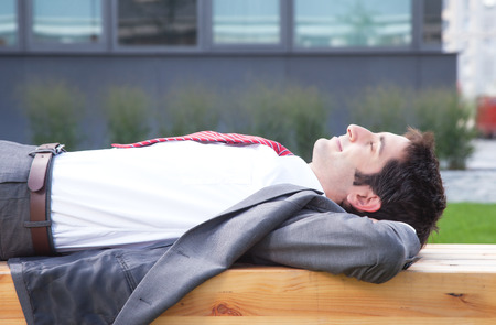 Businessman with black hair relaxing outside photo
