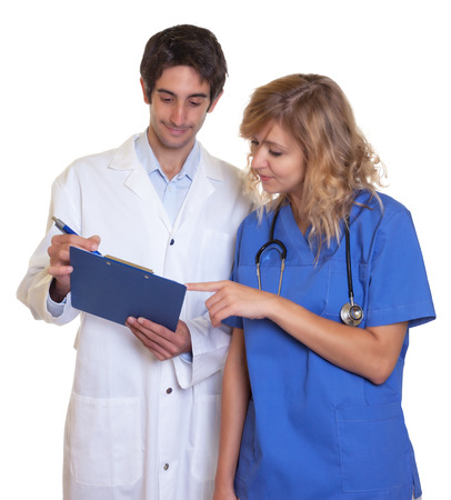 Doctor and nurse looking at clipboard photo