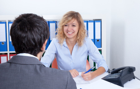 Attractive business woman speaking with a client photo