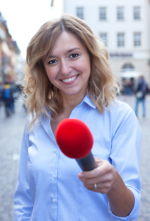 respondent: Interview of a young woman with blond hair in the city Stock Photo