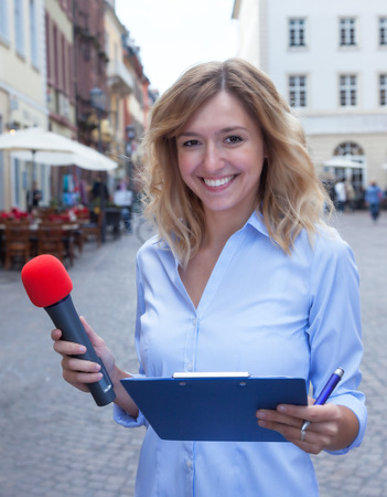 respondent: Attractive woman with blond hair asking people Stock Photo