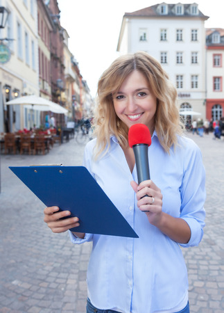 respondent: Female journalist with microphone in the city Stock Photo